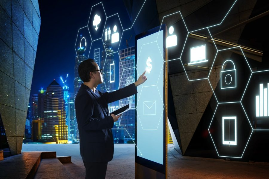 Businessman touches money icon on large digital screen